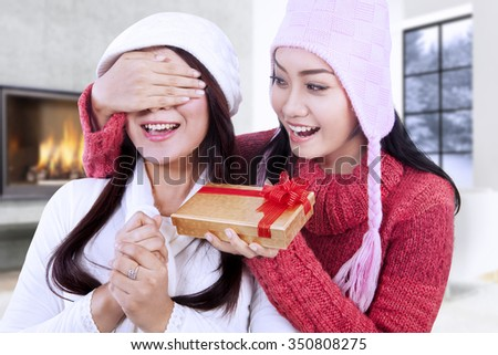 Picture of beautiful young woman giving christmas gift on her friend while wearing winter clothes at home