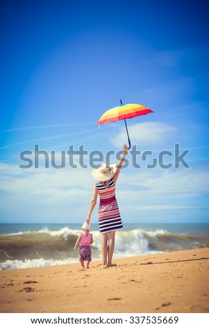 Picture of beautiful young woman holding rainbow umbrella with baby walking on seashore. Backview of happy family on blurred summer sky outdoor background.