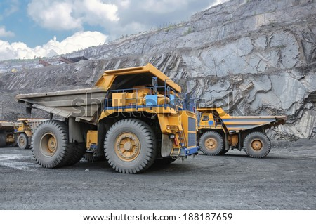 picture of big yellow heavy trucks in open cast mine - stock photo