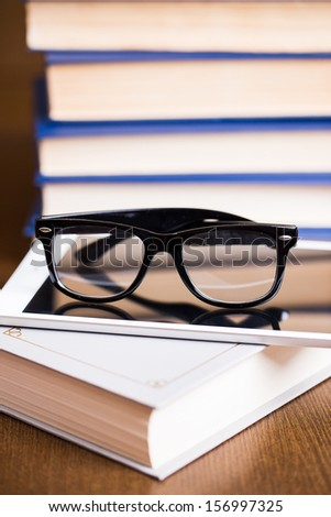 Picture of black glasses on a white book and a tablete