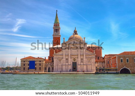 Picture of boat on the canal in Venice, on the background of one of the old part of town with colorful houses and a church. - stock photo