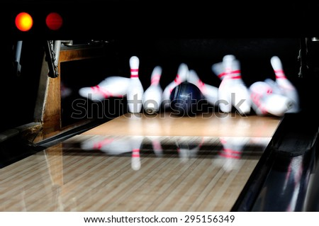 Picture of  bowling ball hitting pins scoring a strike - stock photo