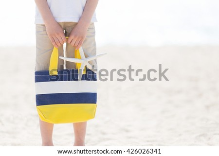 picture of boy holding colorful beach bag and starfish at the beach with no face visible with copyspace on the side, vacation concept - stock photo