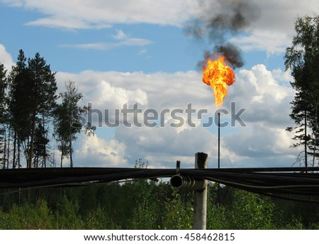 Picture of burning oil gas flare against blue sky
