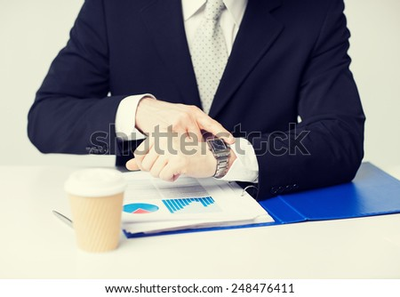 picture of businessman with graphs pointing at watch
