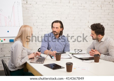 Picture of businesspeople working at table in iffice and discussing difficult business issues connected with companies, firms and enterprises. - stock photo