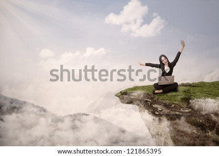 Picture of businesswoman with arms raised while sitting with her laptop on mountain - stock photo