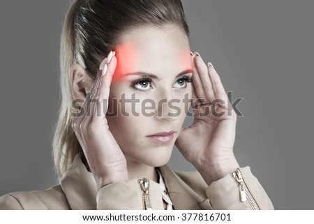 Picture of businesswoman with headache over grey background - stock photo