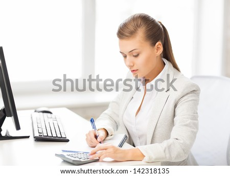 picture of businesswoman with notebook and calculator - stock photo