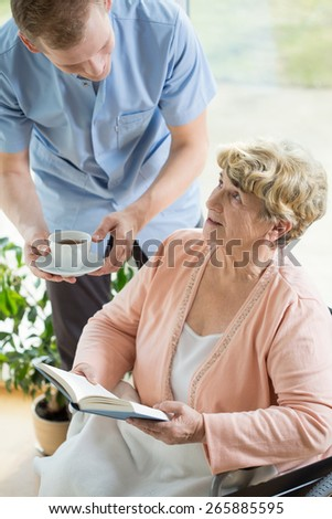 Picture of caregiver helping disabled female pensioner - stock photo