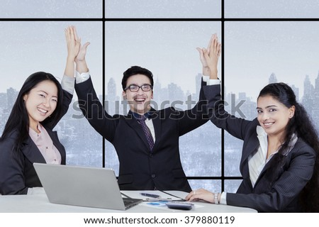 Picture of cheerful businesspeople clapping hands together in the office to celebrate a good job - stock photo