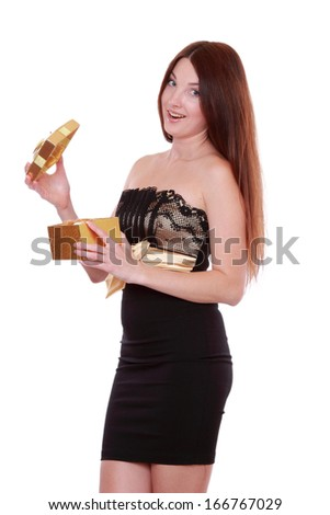 picture of cheerful girl in black and gold dress with gift box isolated over white background on Holiday theme/ - stock photo