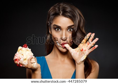 Picture of cheerful girl in blue dress eating  piece of cake - stock photo
