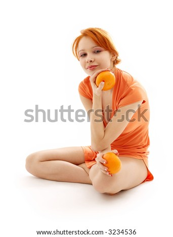 Picture of cheerful redhead with two oranges over white - stock photo