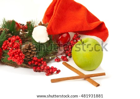 Picture of christmas cinnamon, green apple, santa hat isolated on white
