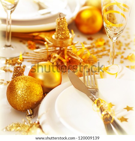 Picture of Christmas table setting still life, festive white utensil decorated with golden candle and shiny xmas tree ball toys, romantic holiday dinner, New Year party, luxury table decorations - stock photo