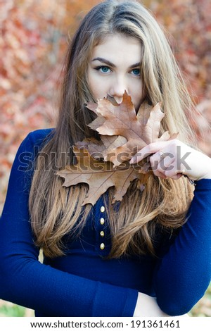 Picture of closeup portrait of beautiful woman hiding face behind autumn brown leaf outdoors background