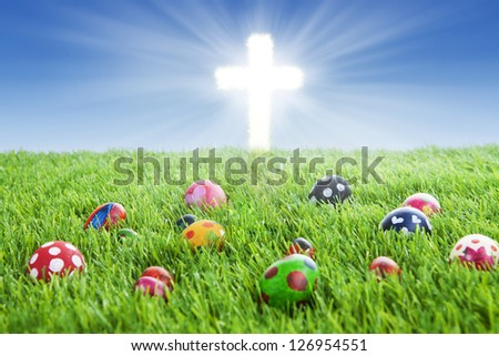 Picture of colorful easter eggs laying on the grass with a bright Cross - stock photo