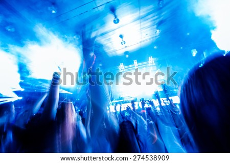 Picture of concert, music festival,party in nightclub, dance floor, disco club, many people standing with raised hands up. Blurred motion in night light rays. - stock photo