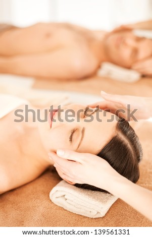picture of couple in spa salon getting face treatment - stock photo