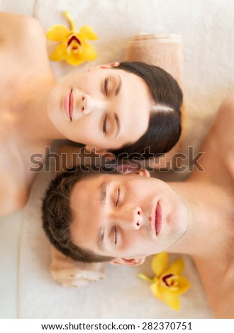 picture of couple in spa salon lying on the massage desks - stock photo