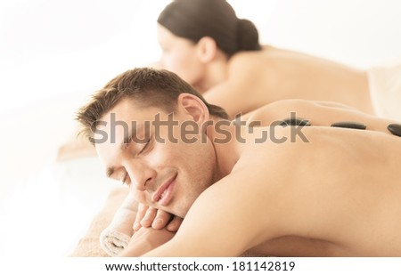 picture of couple in spa salon with hot stones - stock photo