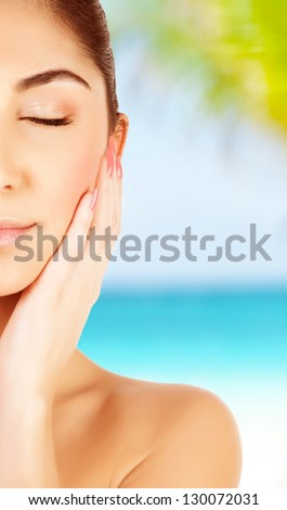 Picture of cute brunette girl with closed eyes enjoying tropical nature, woman tanning on the beach, half face, skin care, natural makeup, day spa near sea, luxury lifestyle, travel and vacation - stock photo