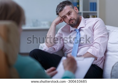 Picture of despair young businessman during psychotherapy session - stock photo