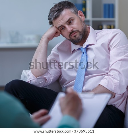 Picture of despair young businessman during psychotherapy session