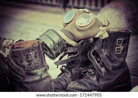 Picture of dirty old used boots and a gasmask  - stock photo