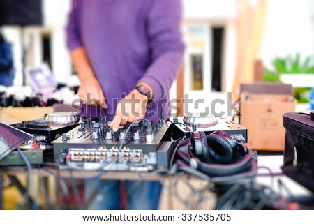 Picture of dj mixing audio tracks with professional musical equipment. Closeup of male hands and equalizer on blurred outdoor background. - stock photo