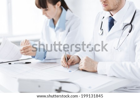 picture of doctor and nurse writing prescription paper - stock photo