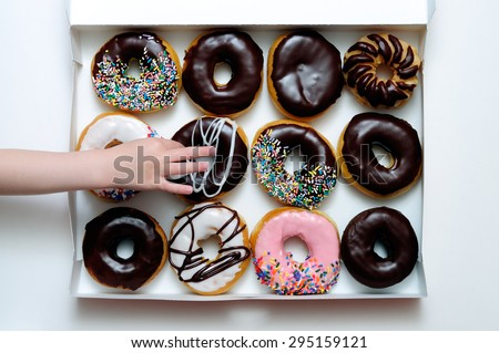 Picture of doughnut box with a child's hand grabbing a doughnut - stock photo