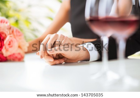 picture of engaged couple with wine glasses in restaurant - stock photo