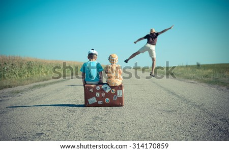 Picture of excited man jumping and two children sitting on old suitcase on country road. Backview of family having fun and waiting on blue sky sunny outdoors background. - stock photo