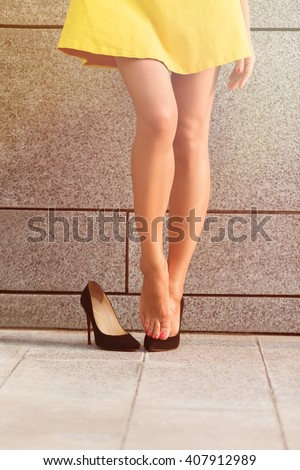 Picture of exhausted woman's legs in full length after hard working day. Girl posing near brick wall. She put off one of her heels. Toned image. - stock photo