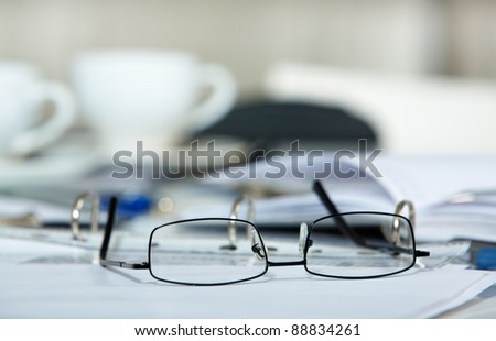 Picture of eyeglasses and blank papers on the table
