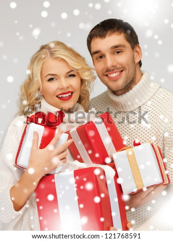 picture of family couple in a sweaters with gift boxes