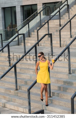 Picture of fashion girl with orange cocktail trying to sit on hand-rail. Girl in sunglasses smiling and having fun on stairs of office building.