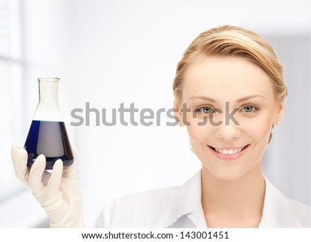 picture of female chemist holding bulb with chemicals - stock photo