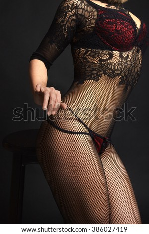 Picture of female model body in fishnet hosiery, sexual  red lingerie,  slim attractive legs, dark background - stock photo