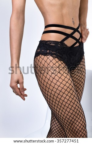 Picture of female model legs in fishnet hosiery - stock photo