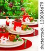 Picture of festive table setting, red cup for tea full of different Christmastime decoration, small Santa Clause decor with yellow candle on white white plate on Christmas tree background - stock photo