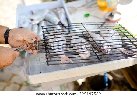 Picture of fish prepared for grill in sunny day. Male hand closing metal grid with four fish on blurred countryside background.