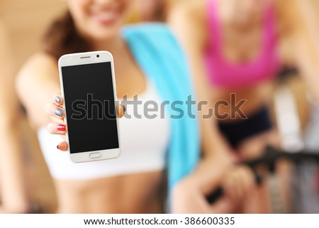 Picture of fit woman holding smartphone in gym