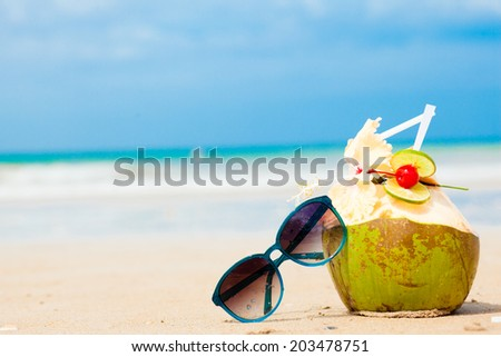 picture of fresh coconut cocktail and blue sunglasses on tropical beach - stock photo