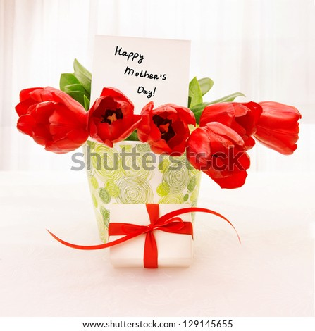 Picture of fresh red tulip flowers in beautiful vase with paper greeting postcard on the table, little white gift box with ribbon, home interior, happy mothers day, festive still life, love concept - stock photo