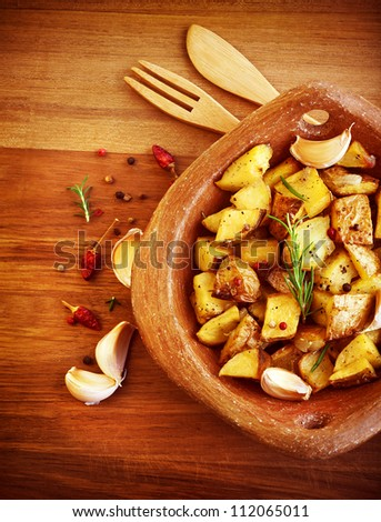Picture of fried potato with garlic and spices on wooden table, baked quartered potato with vegetables serve in wooden plate with knife and fork, homemade french fries, restaurant dish - stock photo