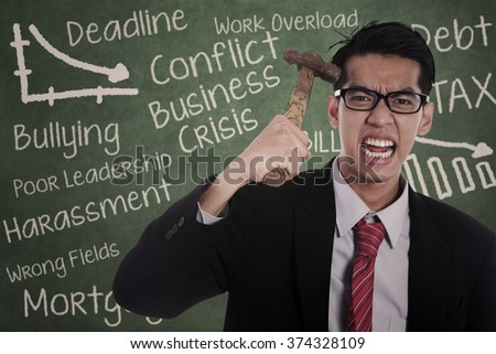 Picture of frustrated businessman hitting his head with hammer in front of blackboard