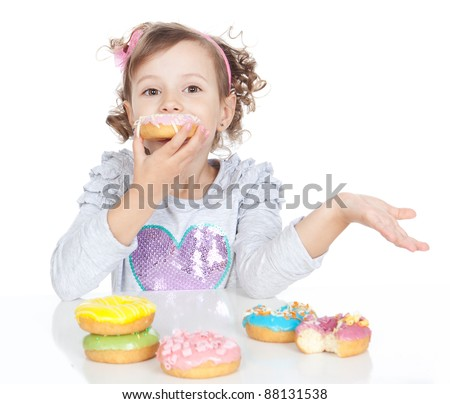Picture of funny little girl eating pink donut on white background - stock photo